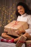 Frau, die Weihnachtsgeschenk hält Stockbild