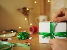 Frau, die Weihnachtsgeschenk mit grünem Band hält lizenzfreies stockfoto