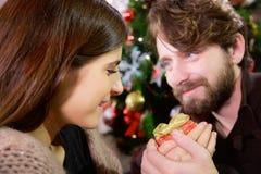Frau, die Weihnachtsgeschenk vom Freund empfängt stockbild