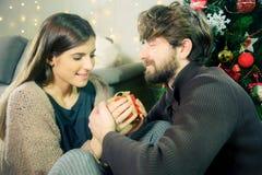 Frau, die Weihnachtsgeschenk vom mittleren Schuss des Freundes empfängt stockfoto