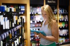 Frau, die Wein unter Verwendung der Auflage wählt Stockfoto