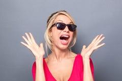 Frau, die wie Stern unter Verwendung beider Hände und Gesichtsausdrucks nach Überraschung sucht Lizenzfreie Stockfotos