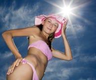Frau, die wieder im rosafarbenen blauen Himmel des Bikinis aufwirft Stockfotografie