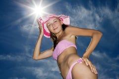 Frau, die wieder im rosafarbenen blauen Himmel des Bikinis mit aufwirft Stockfotografie