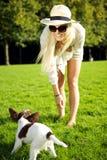 Frau, die Wiith Hund im Park spielt Stockfotografie