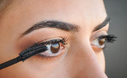 Frau, die Wimperntusche auf ihren Augen anwendet Lizenzfreie Stockbilder