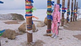 Frau, die in Winterspitzenberge draußen gehen genießt Buddhistische Ritualpfosten mit farbigen Bändern im Winter an stock footage