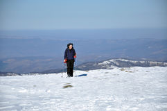 Frau, die Wintertrekking in den Bergen tut Stockbilder