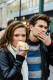 Frau, die Würstchen während Mann-Reinigungs-Mund isst Stockfotos