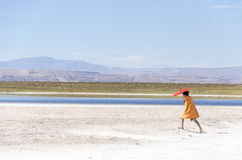 Frau, die in Wüste mit Regenschirm geht Lizenzfreie Stockbilder
