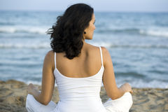 Frau, die Yogaübung auf dem Strand bildet Stockfotografie