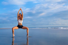 Frau, die Yogaübung auf Strand tut Stockfoto