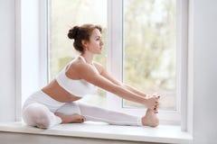 Frau, die Yoga asana auf Fensterbrett tut Stockfotografie