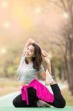 Frau, die in Yoga asana am Naturgarten aufwirft Lizenzfreie Stockbilder