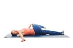 Frau, die Yoga asana Parivrtta-ardha pawanmuktasana lokalisiert tut Lizenzfreie Stockfotos