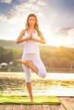 Frau, die Yoga auf dem See - schöne Lichter tut lizenzfreie stockfotos