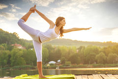 Frau, die Yoga auf dem See - schöne Lichter tut stockfotos