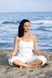 Frau, die Yoga auf dem Strand macht stockfoto