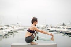 Frau, die Yoga auf Marinepier tut - entspannend in der Natur lizenzfreie stockfotografie