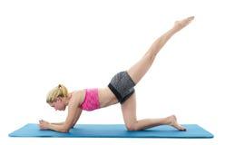 Frau, die Yoga auf Matte tut Lizenzfreie Stockfotografie