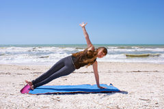 Frau, die Yoga auf Strand in der seitlichen Planke tut Stockfotos