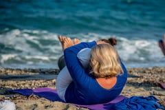 Frau, die Yoga auf Strand tut Lizenzfreie Stockfotos