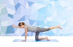 Frau, die Yoga in balancierender Tabelle aufwerfen lässt auf Matte Stockbilder