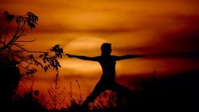 Frau, die Yoga bei dem Sonnenuntergang tut stock footage