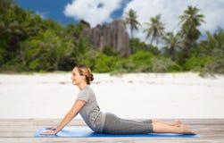 Frau, die Yoga in der Hundehaltung auf Strand tut Stockfotos