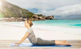 Frau, die Yoga in der Hundehaltung auf Strand tut Lizenzfreies Stockfoto