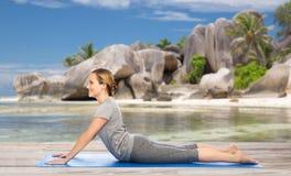 Frau, die Yoga in der Hundehaltung auf Strand tut Lizenzfreie Stockfotografie