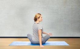 Frau, die Yoga in der Torsionshaltung auf Matte macht Stockbilder