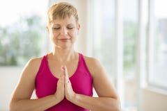 Frau, die Yoga an der Turnhalle tut Stockfotografie