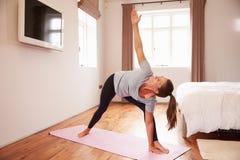 Frau, die Yoga-Eignungs-Übungen auf Mat In Bedroom tut stockfoto