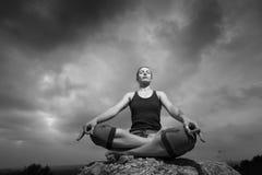 Frau, die Yoga gegen die untergehende Sonne tut Stockfoto