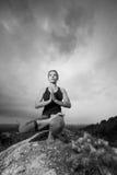 Frau, die Yoga gegen die untergehende Sonne tut Lizenzfreie Stockfotos