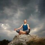 Frau, die Yoga gegen die untergehende Sonne tut Lizenzfreies Stockfoto