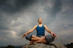 Frau, die Yoga gegen die untergehende Sonne tut Stockbild