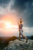 Frau, die Yoga gegen die untergehende Sonne tut Lizenzfreie Stockbilder