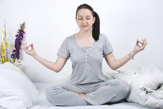 Frau, die Yoga im Bett tut Stockfotos