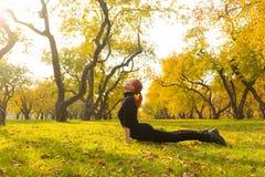 Frau, die Yoga im Herbstpark tut lizenzfreies stockbild