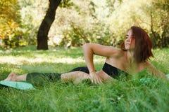 Frau, die Yoga im Park tut Stockfotos