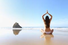 Frau, die Yoga im Strand ausübt stockbild