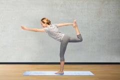Frau, die Yoga in Lord der Tanzhaltung auf Matte macht Stockfoto