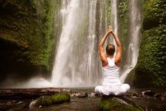 Frau, die Yoga nahe Wasserfall tut lizenzfreie stockbilder