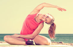 Frau, die Yoga am Seestrand ausübt Lizenzfreies Stockbild