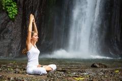 Frau, die Yoga zwischen Wasserfällen tuend meditiert Lizenzfreie Stockfotografie
