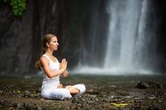 Frau, die Yoga zwischen Wasserfällen tuend meditiert Stockfotografie