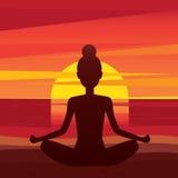 Frau, die in Yogahaltung padmasana auf dem Strand sitzt Lizenzfreies Stockbild