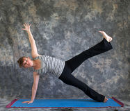 Frau, die Yogalage Vasisthasana tut Lizenzfreie Stockfotografie